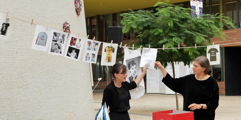 Kunstausstellung: Zwei Frauen stehen vor einer Wäscheleine und einem Bügelbrett und hängen Informationen für die Besucher an die Leine