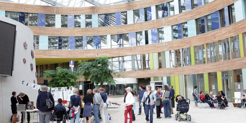"""Besucher sehen sich die Kunstausstellung """"Der Weg eines T-Shirts rund um den Globus"""" im Atrium im UBA Dessau an."""