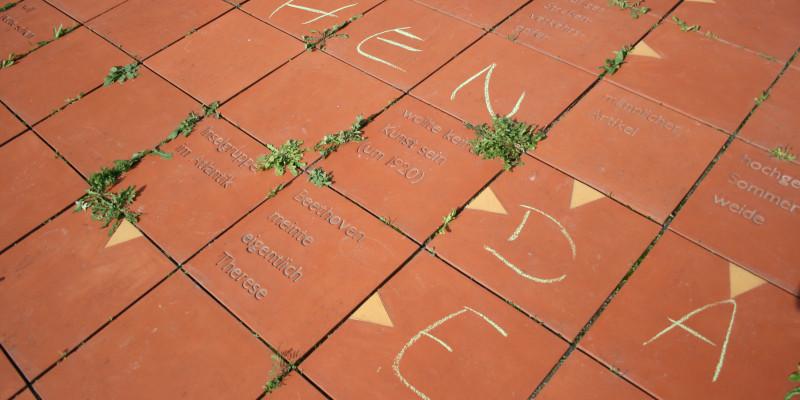 Kreuzworträtsel: Nahaufnahme der Terrakotta-Platten mit Inschrift