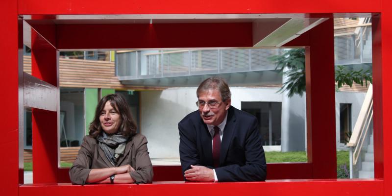 Regine Bittner, stellvertretende Direktorin der Stiftung Bauhaus, und Vizepräsidenten des Umweltbundesamtes, Thomas Holzmann, stehen zusammen unter dem XXL-Stuhl