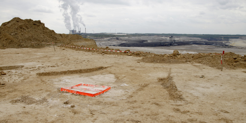 Eine karge Bergbau Landschaft, im Hintergrund eine Energieanlage, vorne sieht man den roten Rahmen, mit dem die Künstlerin einen Bodenabdruck macht.