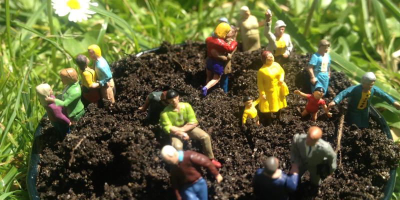 Ein Eimer voller Erde steht auf einer Wiese, darin stecken mehrere Spielzeugfiguren.