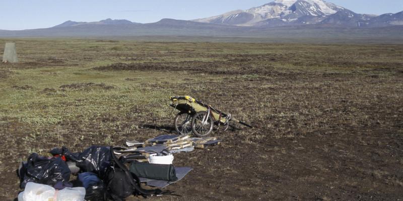 Eine weite Steppenlandschaft, im Hintergrund schneebedeckte Berge. Im Vordergrund der Handwagen der Künstlerin mit ihrem Gepäck.