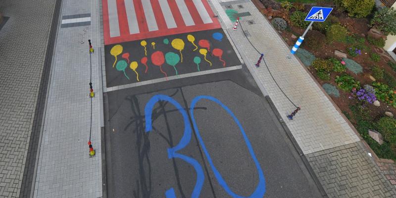 Blick auf die bunt gestaltete Kreuzung mit markierten Zebrastreifen und 30-er-Zone
