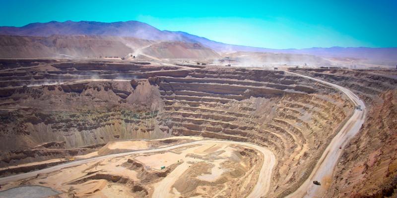 Panoramaufnahme einer Kupfermine: Vorblauen Himmel sieht man die vielen abgetragenen Erdschichten, eine gigantische Kluft.