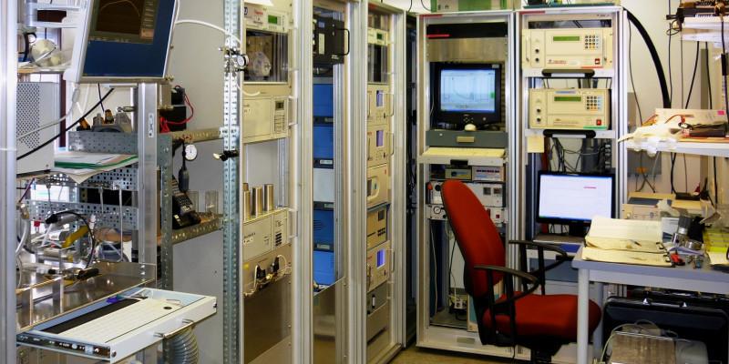 Messraum des Umweltbundesamts in einer Luftmessstation mit mehreren Motioren, Computer, Messgeräten und einem PC-Arbeitsplatz