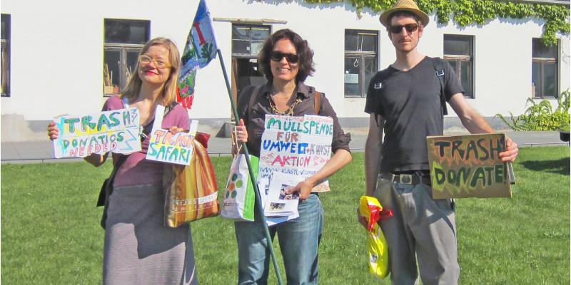 Zwei Frauen und ein Mann halten Schilder hoch, dass sie auf der Suche nach Müll sind. Sie stehen auf einer Wiese vor einem Haus.