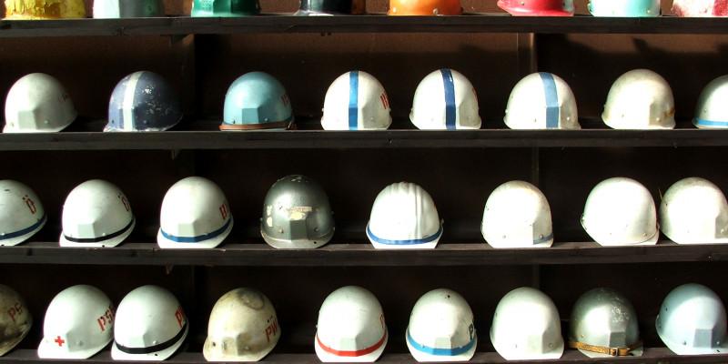 Regal mit verschieden farbigen Sicherheitshelmen für Arbeiter und Arbeiterinnen
