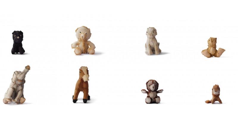 Kleine ganz unterschiedliche Secondhand-Kuscheltiere sitzen in einer Reihe
