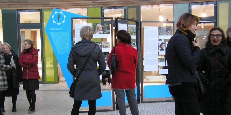 Mehrere Personen schauen sich die Austellung (Schautafeln) im Atrium des Umweltbundesamtes in Dessau an.