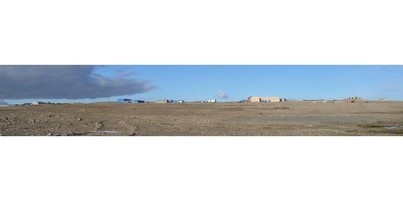 Im Hintergrund stehen einige Hallen und Häuser, vorne ist die karge Landschaft der Arktis zu sehen.