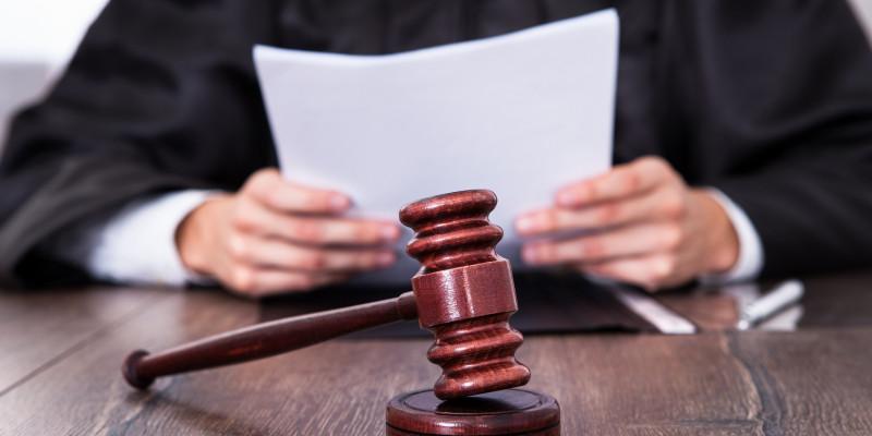 Ein Richter mit Hammer und Verhandlungsunterlagen sitzt an einem Tisch.
