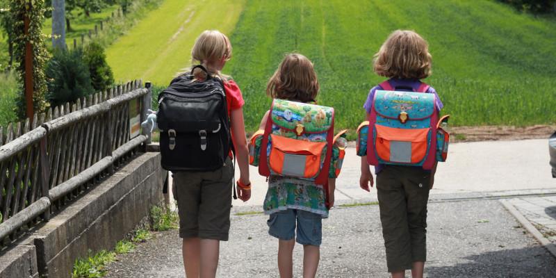 Drei Kinder gehen zusammen zu Fuß zur Schule, sie tragen Schulranzen auf dem Rücken.