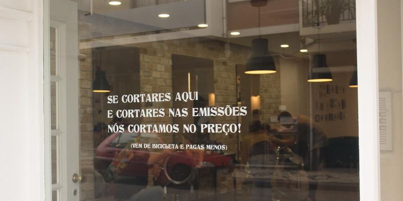 """Aufschrift auf dem Schaufenster: """"Ihr kommt mit dem Rad zu uns und senkt damit die Emissionen, dann senken wir den Preis Eures Haarschnitts"""""""