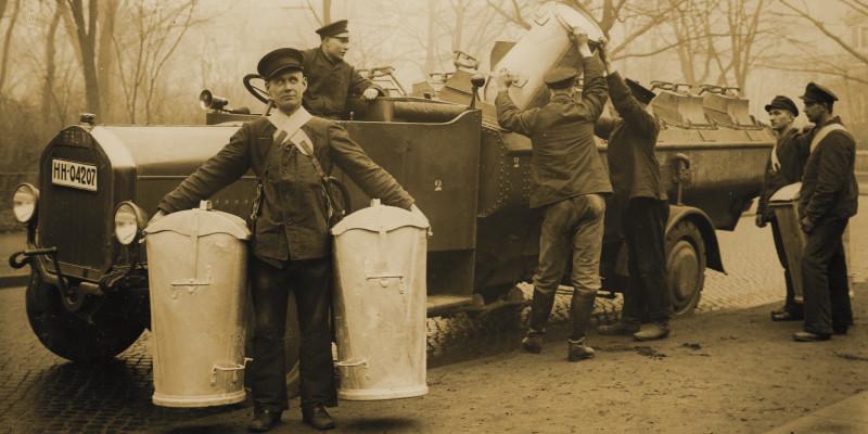 Mehrere Arbeiter entleeren Eimer in ein Müllfahrzeug