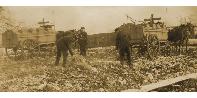 Arbeiter sortieren Abfall mit Heuharken