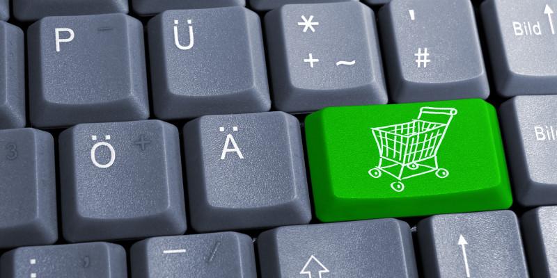 Schwarze Tastatur mit einer grünen Taste, auf der ein Einkaufswagen zu sehen ist