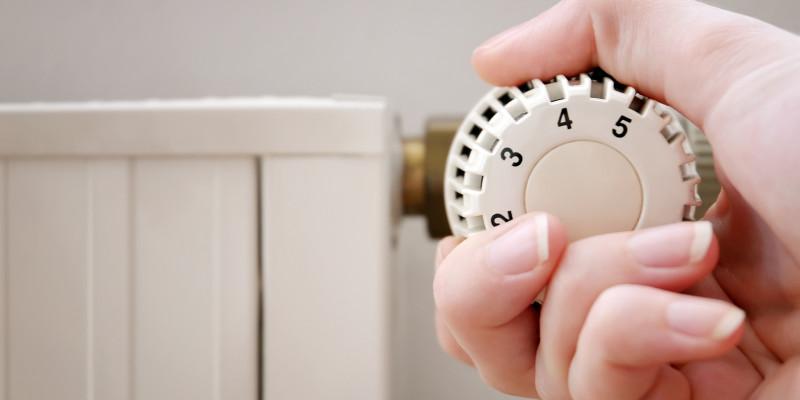 Nahaufnahme: Eine Hand dreht das Thermostat einer Heizung auf.