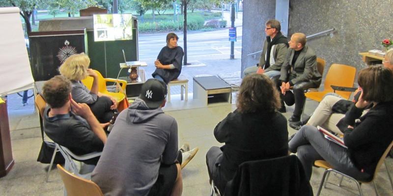 Diskussionsrunde im utopischen Institut: 9 Personen sitzen in einem Stuhlkreis