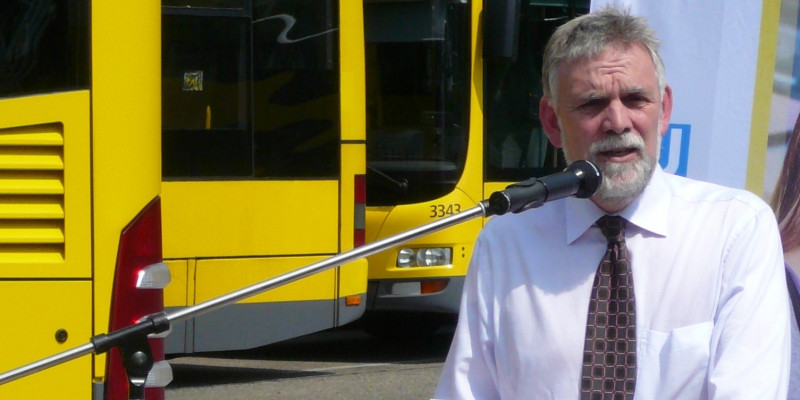 the former UBA President Jochen Flasbarth making a speech, in the background yellow busses