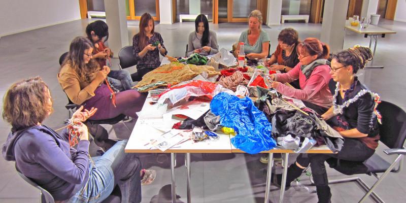 Neun Frauen sitzen an einem Tisch und arbeiten mit Wolle, Stoff und Müll