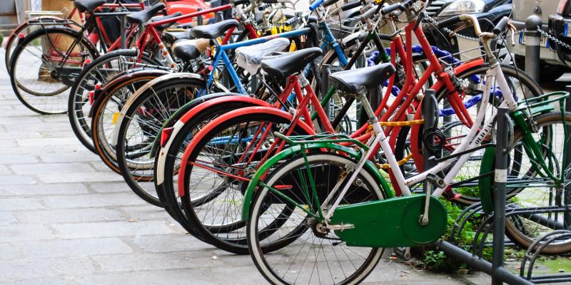 Im Fahrradständer abgestellte bunte Fahrräder.
