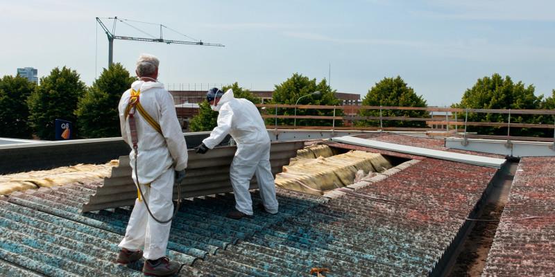 Zwei Bauarbeiter in weißen Schutzanzügen und Atemschutzmasken auf einem Wellasbestdach.