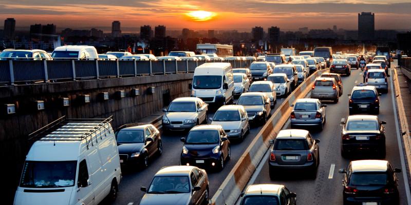 Stau auf der Autobahn am Abend. Ein Sonnenuntergang ist am Horizont zu sehen.