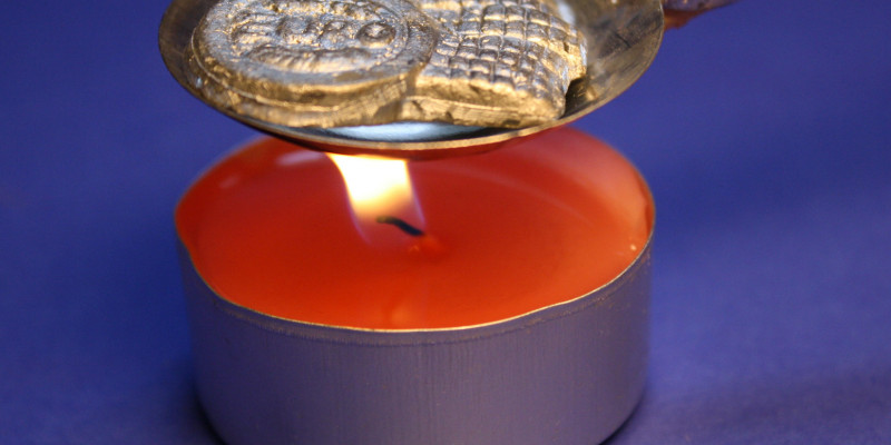 red candle with a spoon for lead pouring