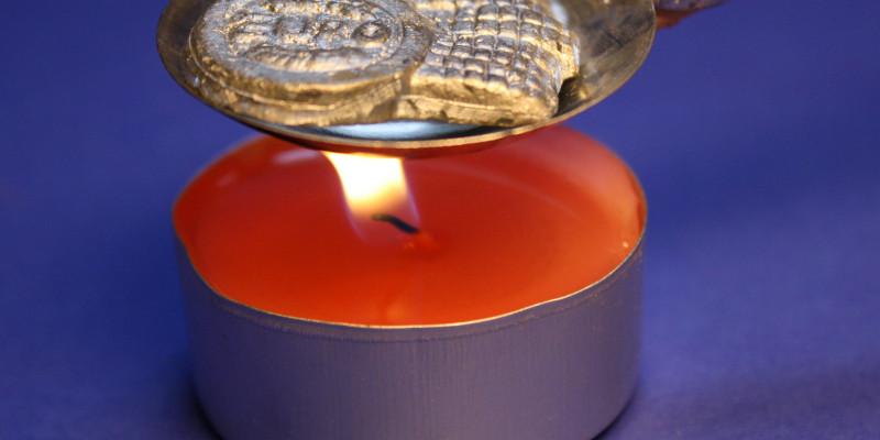 rotes Teelicht mit Löffel zum Bleigießen