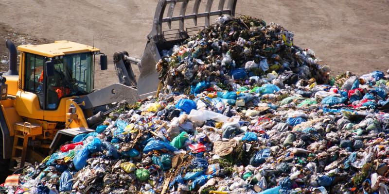 Ein Bagger schiebt den Müll der Abfalldeponie zusammen