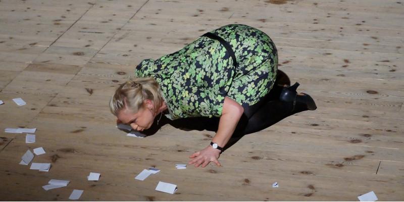 auf dem Boden kniende Frau pustet Papier