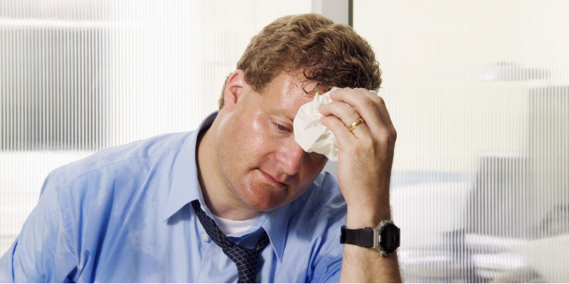 A sweaty man sits in his office in a shirt and tie, wiping his brow.