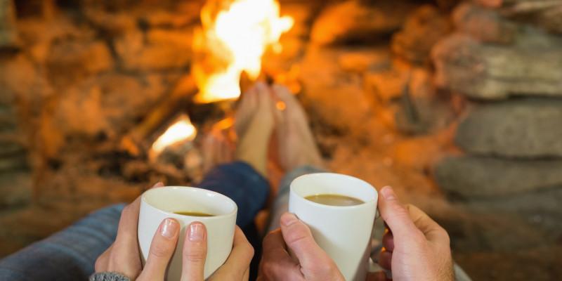Zwei Menschen sitzen vor dem Kamin und halten Teetassen in der Hand.