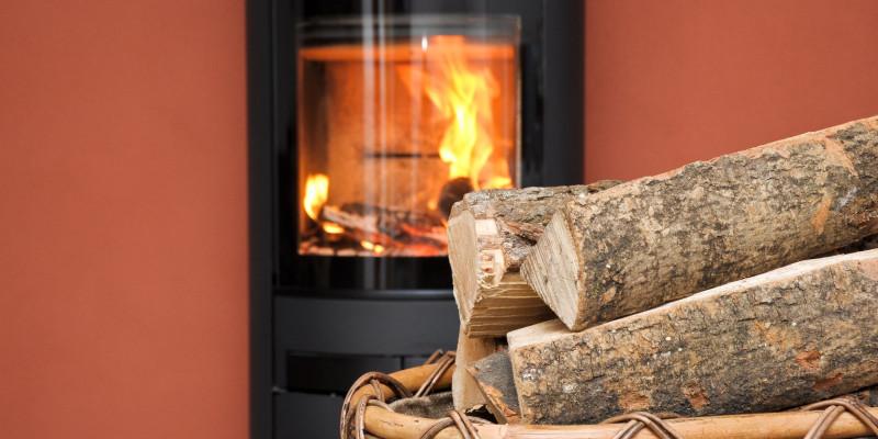 Kamin mit Feuer und Krob mit Holzscheiten