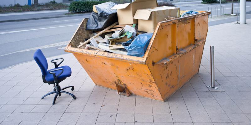 Ein Müllcontainer steht auf der Straße, daneben steht ein Bürostuhl