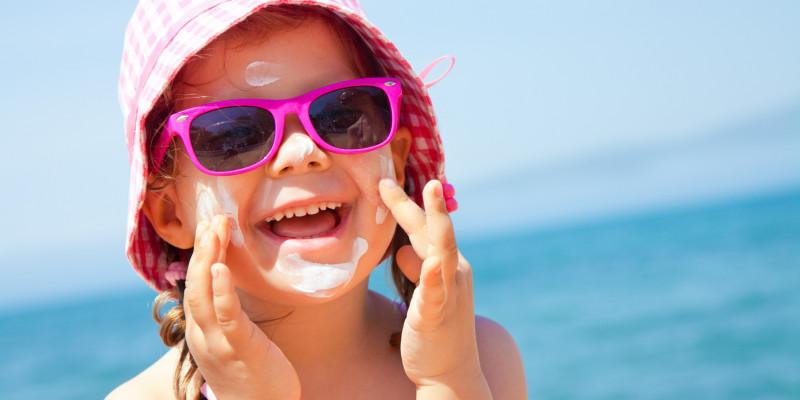Kind sitzt am Strad und cremt sich mit Sonnencreme ein