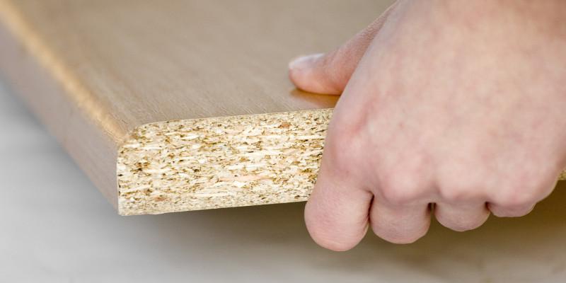 Hand greift nach einer Spanplatte
