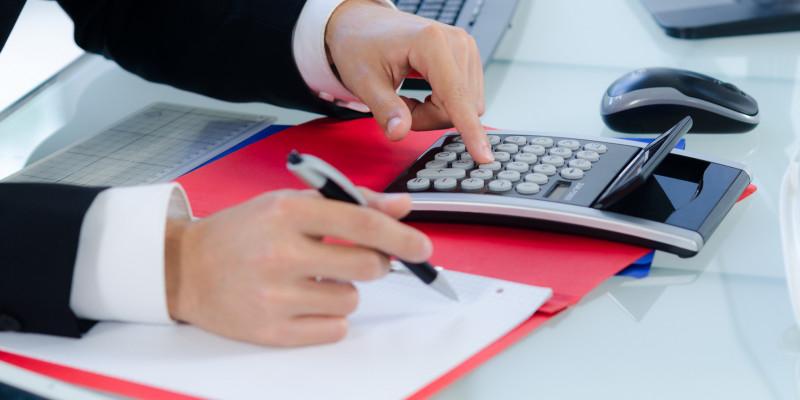 Ein Mann kalkuliert mit dem Taschenrechner die Kosten.