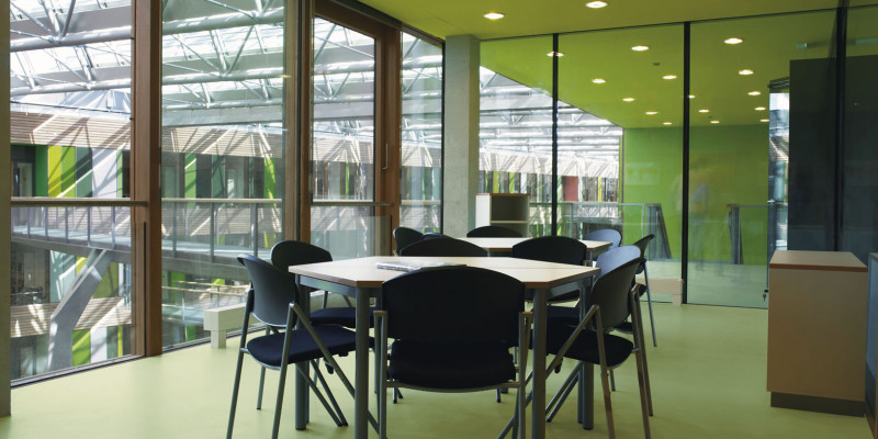 Besprechungsraum mit Tisch und Stühlen, ausgelegt mit elastischem Fußbodenbelag