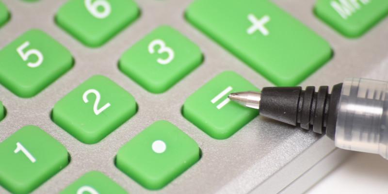 grüne Tasten eine Taschenrechners, wobei ein Kugelschreiber auf = zeigt