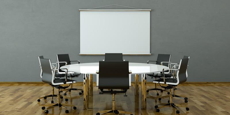 Konferenzzimmer mit hölzernem Bodenbelag, auf dem Tisch und Stühlen stehen