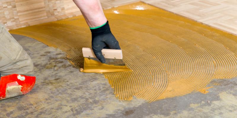 Ein Mann verarbeitet Bodenbelagsklebstoff.