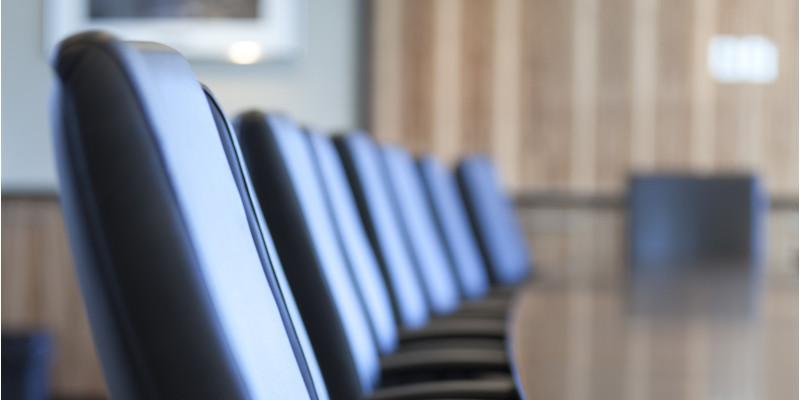gepolsterte Stühle an einem Tisch in einem Sitzungsraum