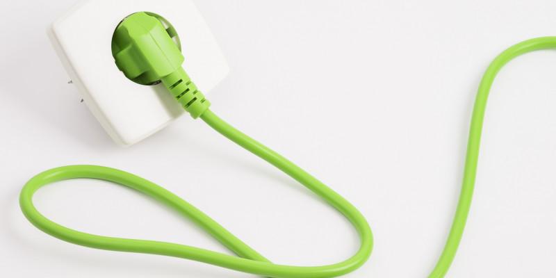 grünes Kabel mit Stecker in der Steckdose