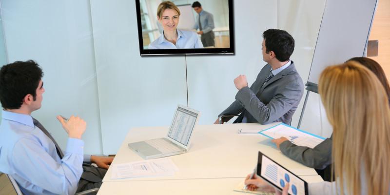 Mehrere Geschäftsleute nehmen an einer Videokonferenz in einem Büro teil.