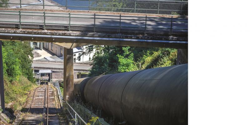 Das Bild zeigt den Blick entlang einer großen Röhre und einer steilen Gleisanlage hinunter zu eine Gebäude und einer nur in einem kleinen Ausschnitt erkennbaren Wasserfläche.
