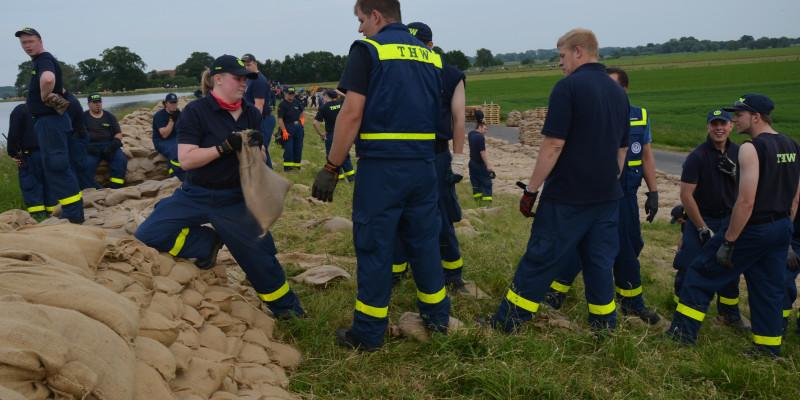 Personen des THW beim Errichten eines Deichs aus Sandsäcken in Flußlandschaft.