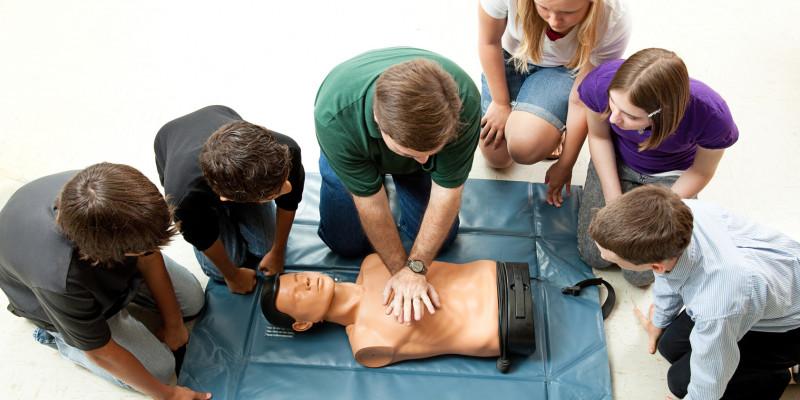Jugendliche üben Herzmassage am Torso einer Übungspuppe im Erste Hilfe Kurs .