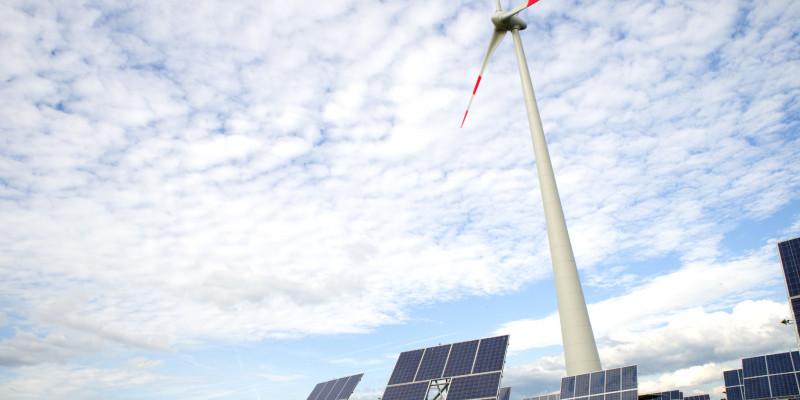 Photovoltaik- und Windenergieanlagen vor blauem Himmel mit Schäfchenwolken.